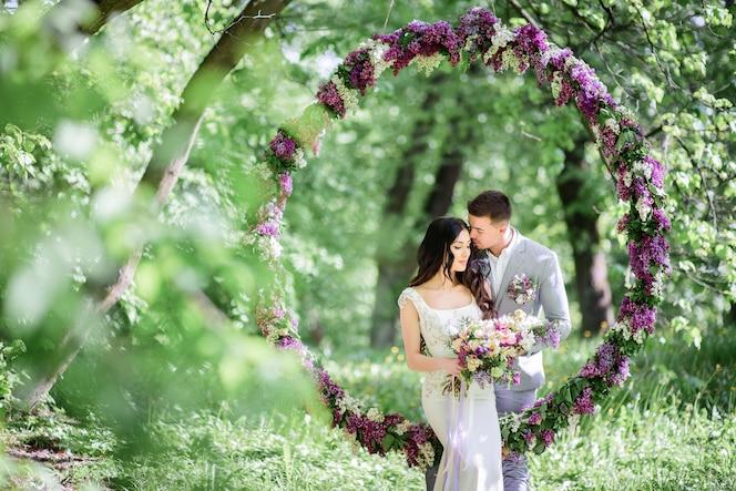 La novia y el novio posan detrás de un gran círculo de lilas en el jardín