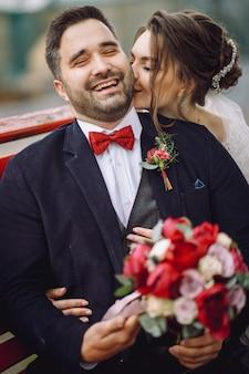 La novia y el novio se divierten abrazándose y besándose en el banco afuera