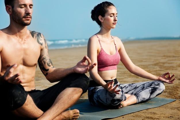 La pareja caucásica medita en la playa