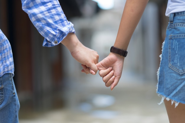 La pareja feliz que lleva a cabo la promesa del meñique de las manos o meñique juro. hombre y mujer enamorados