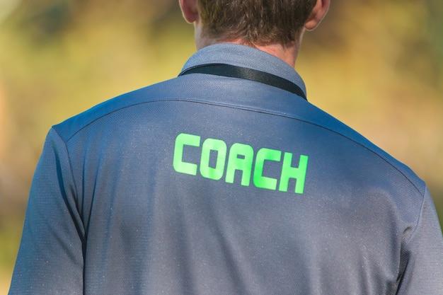 La parte posterior del entrenador deportivo vistiendo una camiseta deportiva con la palabra entrenador escrito en la parte posterior