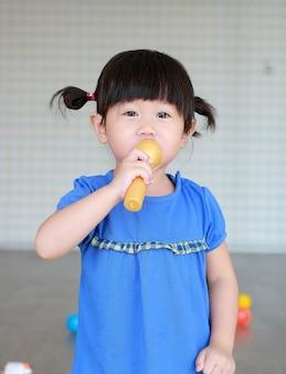 La pequeña muchacha linda del niño asiático canta una canción por el micrófono plástico