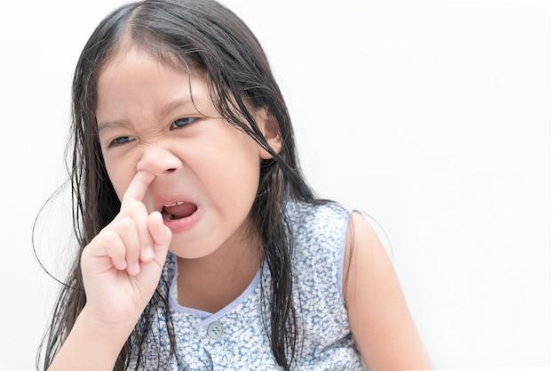 La pequeña muchacha linda escoge su nariz en el fondo blanco, concepto de la atención sanitaria y de la higiene