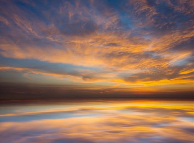 La puesta del sol colorida de la tarde con la nube en el cielo refleja en el mar. la puesta del sol crepúsculo es el tiempo después del sol