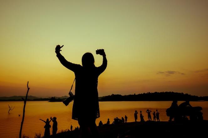 La silueta de una mujer levanta sus manos entre la multitud cerca del agua en la puesta de sol