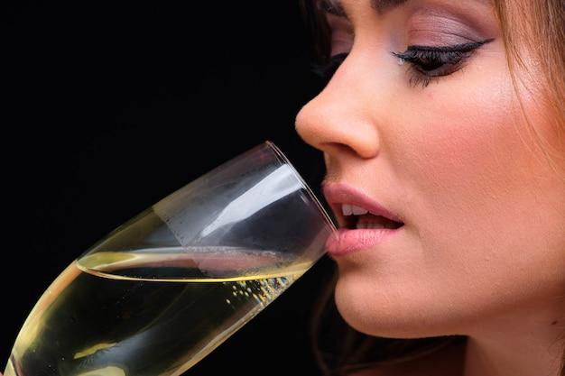 De labios femeninos jóvenes bebiendo champán contra negro