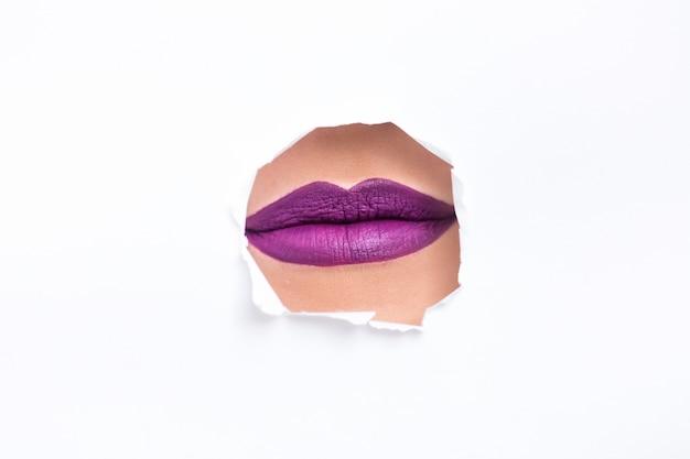 Labios con lápiz labial púrpura en una pared blanca