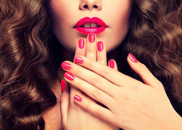 Labios de mujer perfectos con forma ideal coloreada con lápiz labial rosa intenso, manicura del mismo color