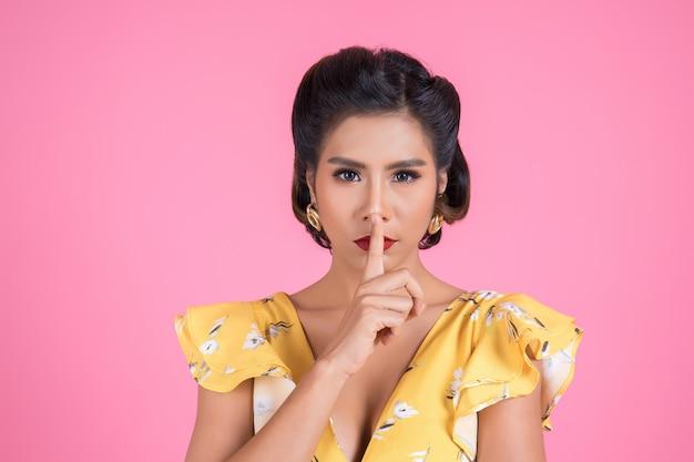 Labios rojos y dedo de la mujer asiática de la belleza que muestran la muestra del silencio del silencio