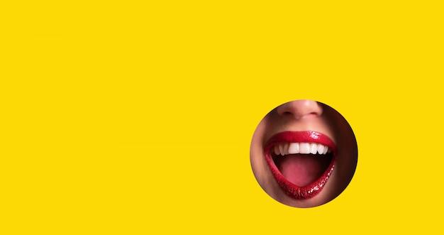 Labios rojos y sonrisa brillante a través del agujero en el fondo de papel amarillo