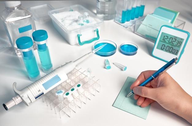 Laboratorio biológico o bioquímico desenfocado, primer en la mano que escribe una nota.