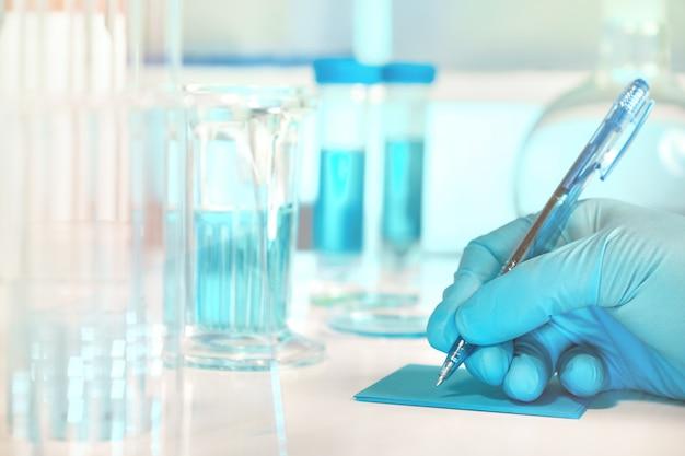 Laboratorio biológico o bioquímico fuera de foco, primer plano en la mano enguantada escribiendo una nota