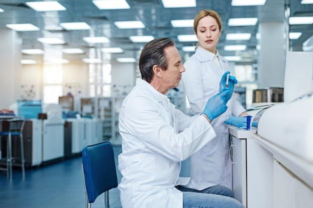 Laboratorio moderno. encantado de mujer vestida con bata blanca y manteniendo la sonrisa en la cara mientras mira hacia abajo