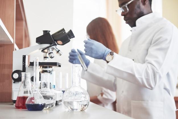 Los laboratorios de laboratorio realizan experimentos en un laboratorio químico en matraces transparentes. fórmulas de salida