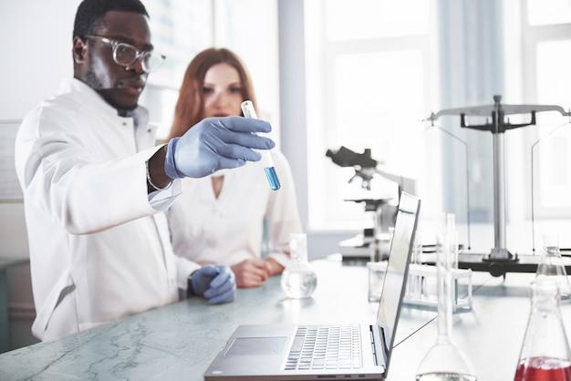 Los laboratorios de laboratorio realizan experimentos en un laboratorio químico en matraces transparentes. fórmulas de salida.