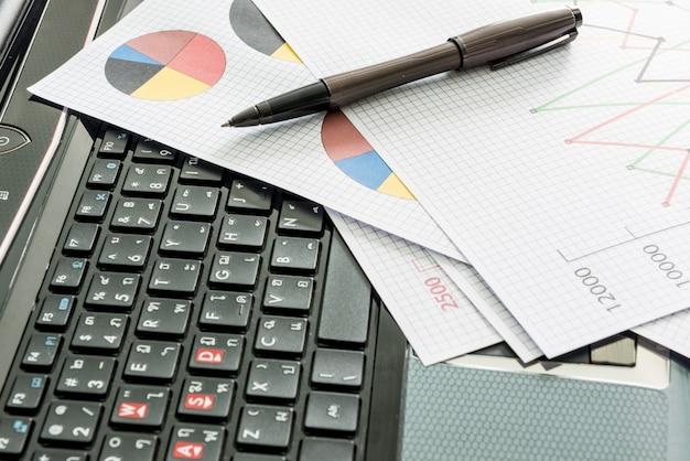 Labtop, tablas financieras, archivo de documento, pluma sobre la mesa