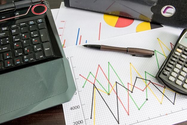 Labtop, tablas financieras, calculadora, archivo de documento, lápiz sobre la mesa