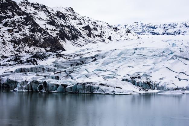 Ladera escarpada y el lago congelado durante el invierno