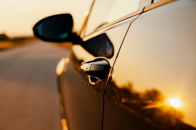 Lado del coche en el fondo de la reflexión del atardecer