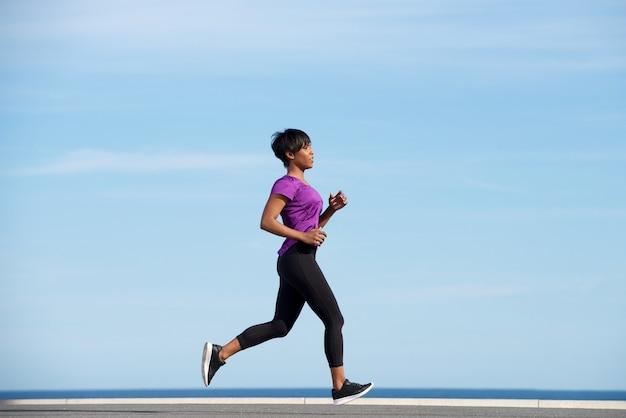 Lado completo del cuerpo ajuste joven mujer africana corriendo al aire libre contra el cielo azul