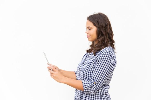 Lado de una estudiante latina positiva usando tableta