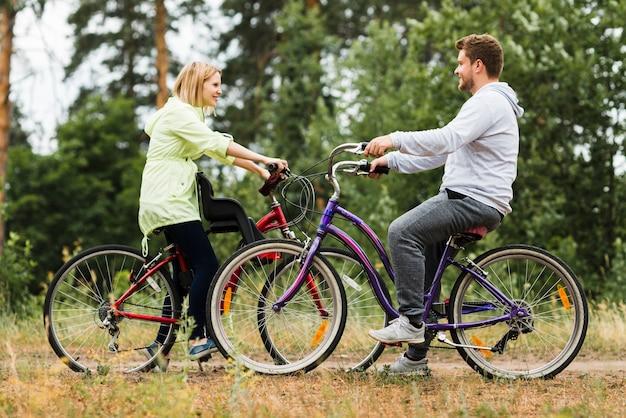 De lado feliz pareja en bicicleta