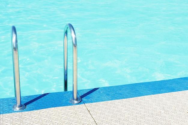 Lado de la piscina, agua de la piscina azul y barandas de escalera de metal.
