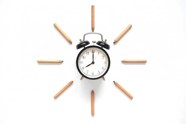 Lado plano creativo de reloj despertador y lápices de colores sobre fondo blanco