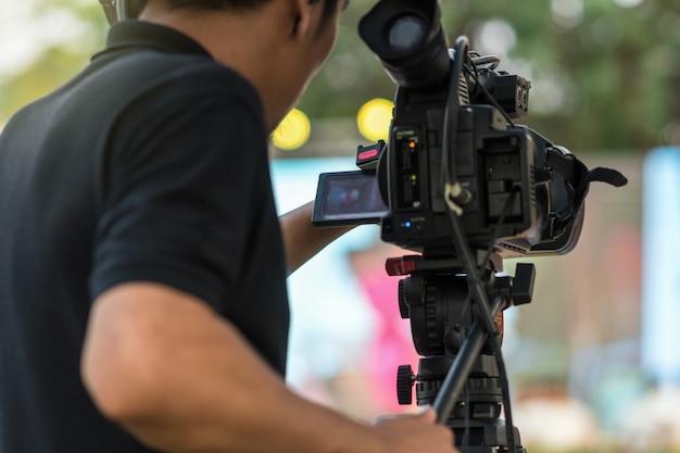 Lado posterior de video cameraman sacando fotos al escenario