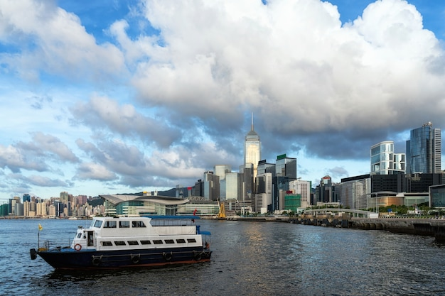 Lado del río de hong kong cityscape en la tarde con el barco del transporte y la nube lisa