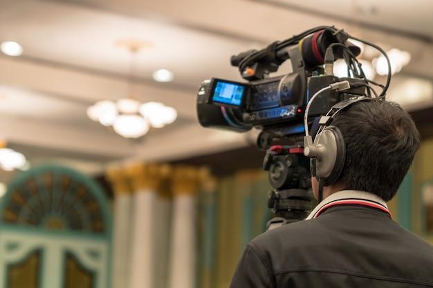 Lado trasero del camarógrafo de video que toma una fotografía al orador asiático con un traje informal