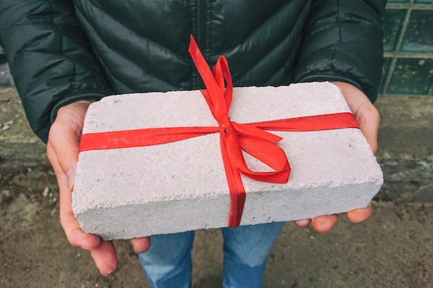 Ladrillo blanco con cinta roja como caja de regalo en manos masculinas