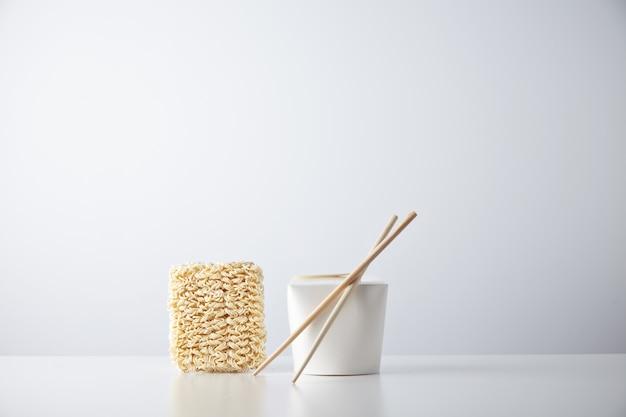 Ladrillo de fideos japoneses secos presentados cerca de una caja de comida para llevar minorista cerrada con palillos