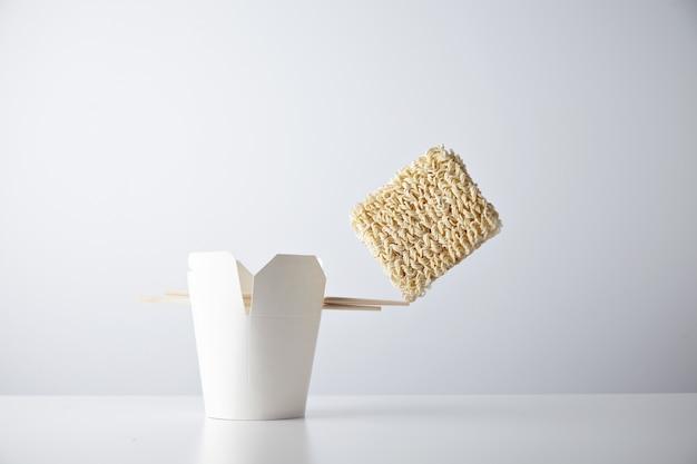 Ladrillo de fideos secos se equilibra en el borde de los palillos en la caja de comida para llevar en blanco aislada en el conjunto minorista comercial blanco