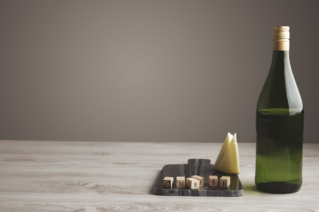 Ladrillo de letra de madera cerca de queso de cabra en rodajas y botella de uva de jugo de vino verde medio vacía aislada en tablero de piedra de mármol sobre mesa de madera blanca y fondo gris neutro