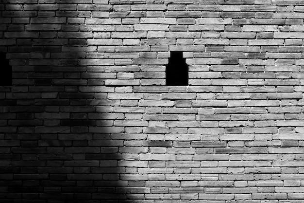 El ladrillo de pared gris está dividido en partes de luz y sombra