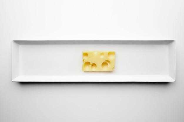 Ladrillo de queso emmental o maasdam aislado en un plato blanco, vista superior