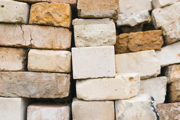 Ladrillos de diferentes tamaños y texturas, fondo de ladrillos apilados.