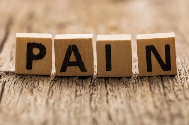 Ladrillos de juguete sobre la mesa con la palabra dolor