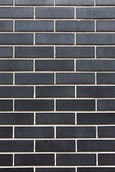 Ladrillos negros de piedra con costuras blancas pared textura fondo vertical disparo