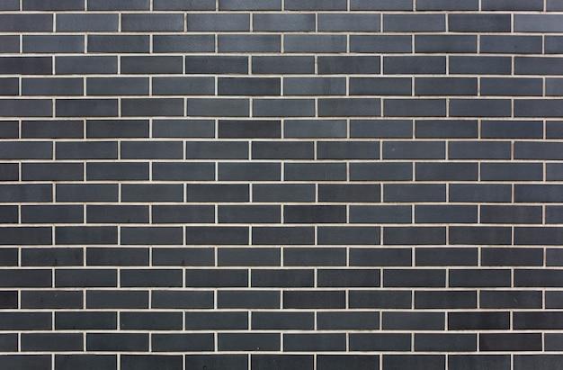 Ladrillos negros de piedra moderna con fondo de textura de pared de costuras blancas