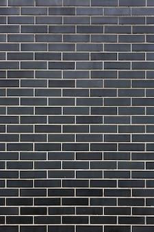 Ladrillos negros de piedra modernos con costuras blancas pared textura vertical de fondo