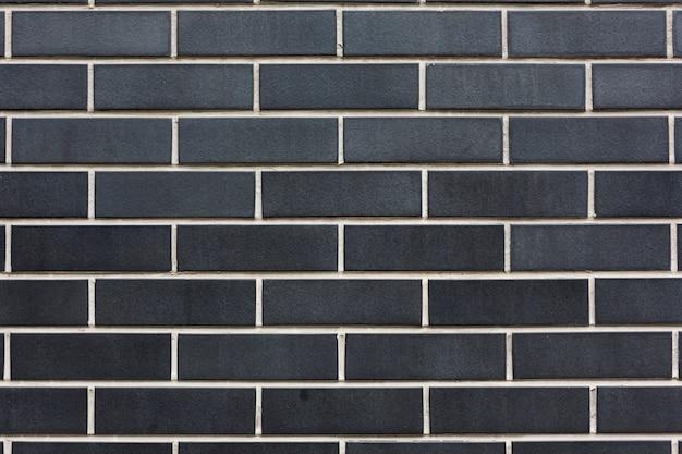Ladrillos de piedra negra con fondo de textura de pared de costuras blancas