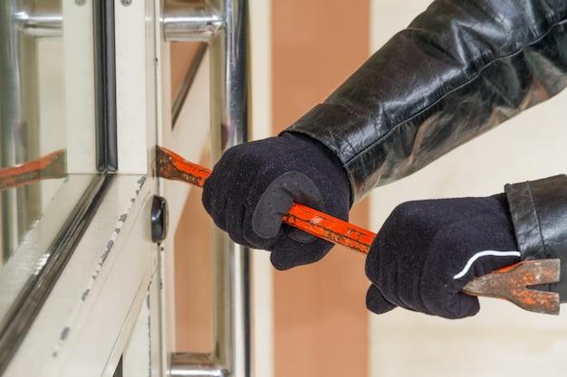 Ladrón con abrigo de cuero rompiendo en una casa