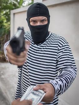 Ladrón apuntando con un arma a tomar dinero del turista víctima en la calle peatonal., concepto de criminalidad