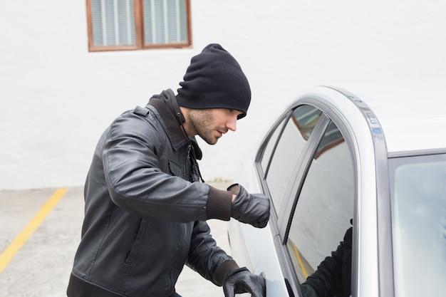 Ladrón entrando en el coche con el puño