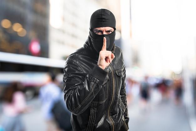 Ladrón haciendo silencio gesto sobre fondo desenfocado