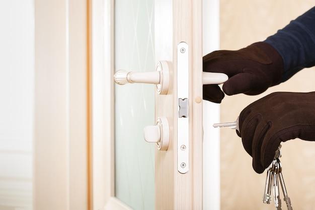 Ladrón con herramientas para abrir cerraduras rompiendo y entrando en una casa. concepto de seguridad.