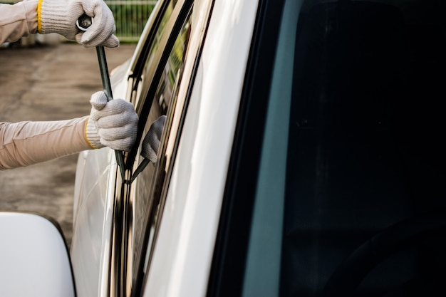 El ladrón está intentando robar el coche. un ladrón abriendo la puerta del auto al entrar.