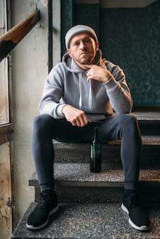 Ladrón masculino con cuchillo sentado en las escaleras